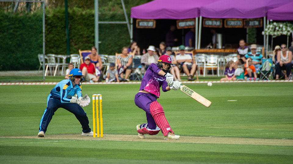 Two female crickets - one holding a bat hitting and ball and one fielding